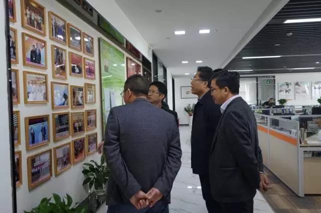 赖厚平董事长带领来宾们来到了广东博皓的文化墙前,向大家简单介绍了一些照片墙上背后的小故事