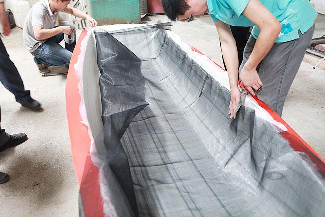 真空导入设备 (点击查看详情)  经过清洗、涂抹脱模水、涂抹脱模剂步骤后,用BUFA胶铺设玻璃纤维毡  铺设正负45度的玻璃纤维轴向布  再铺玻璃纤维毡,将玻纤毡和玻纤布交替铺设多层  铺设脱模布层  铺设真空导流网层  铺设真空袋膜层  用密封胶条将缠绕管和真空袋膜粘住封闭  完成真空导入前处理的小船模具  调配适量的固化剂加入到树脂中  启动设备,开始进行真空导入  真空导入效果  大家查看真空导入演示